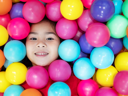 Face of the kid with smiling in the plassic ball pool 스톡 콘텐츠