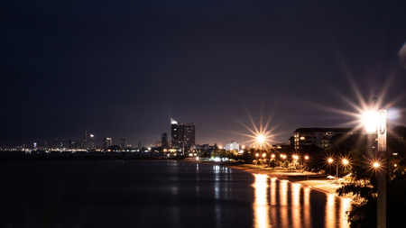 View of the city beside the sea in the night time