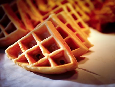 Row of the waffles on the white table for brakefast serve