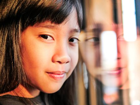 Face of the girl with feeling happy are looking with reflected from the window Imagens