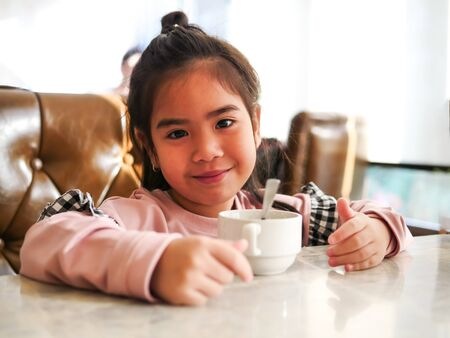 The face of the child with feeling happy with her breakfast milk cup