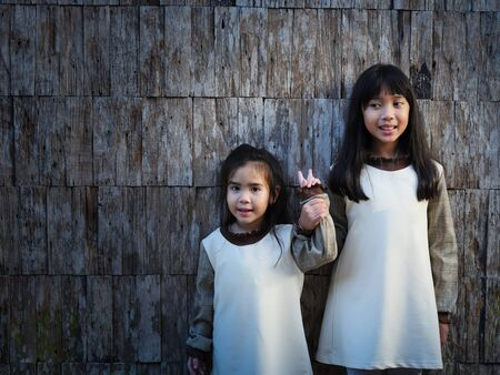 The 2 sisters standing on the wood wall and older sister catch the hand of her sister with smiling