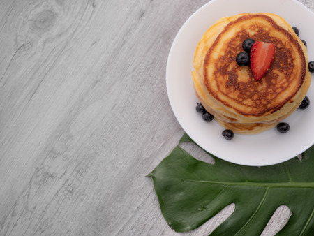 The dish of pancake with strawberry on top on the table with white background 스톡 콘텐츠