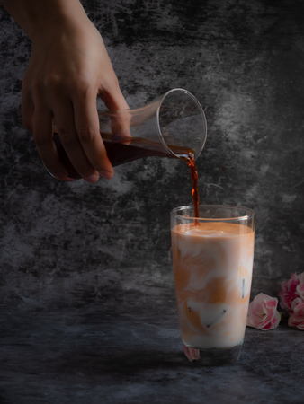 Hand hold the glass of tea puring to mix in the milk with dark background 스톡 콘텐츠