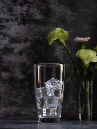 The empty glass with ice put on the floor with dark background