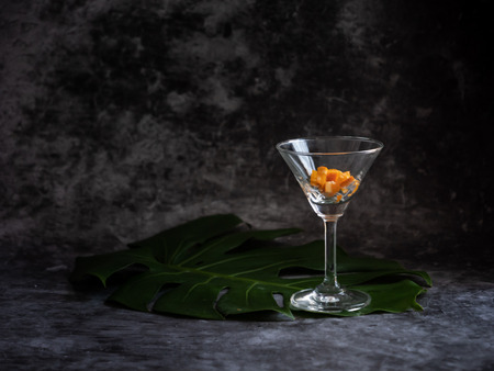 The empty glass put on the table with white background with the leaf on the floor