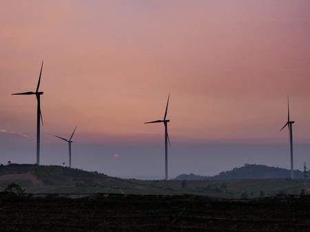 Wind turbine farm on the mountain at sunset time on orange light background 에디토리얼