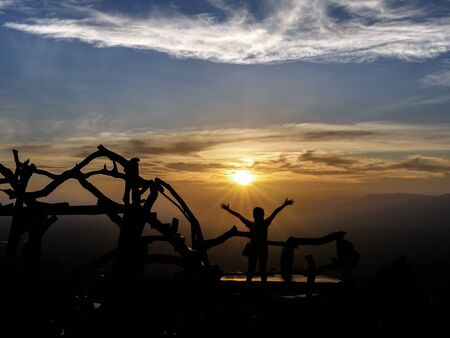 silhouette picture of the woman who was relax on the travel trip in the mountain at the sunset time