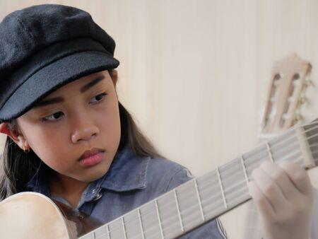 Asian girl was playing guitar Imagens