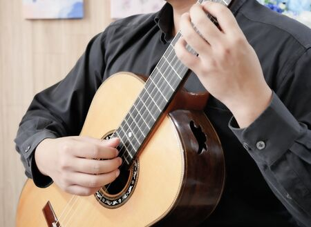 The man with black cloth was playing classic guitar