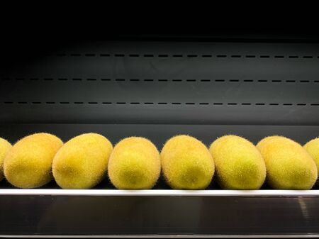The row of kiwi fruit on the shelf for sell