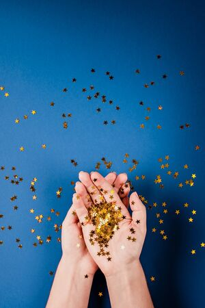 Golden confetti sparkles in female hands on a dark blue background. Christmas concept. Birthday. Background. Stok Fotoğraf