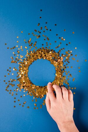 A circle of golden confetti sparkles in female hands on a dark blue background. Christmas concept. Birthday. Background.