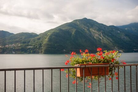 View through the window frame from the room on Lake Como and mountains in good weather.View from the room to the balcony and Lake Como through the glass doors Stockfoto
