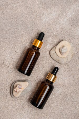 Glass brown bottles of serum with a pipette for skin care is on the sand with stones and shells. Cosmetics with marine components. The concept of health and beauty. minimalism, copy space