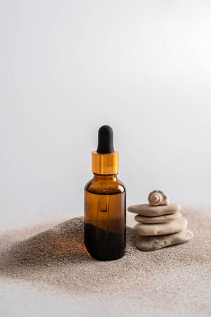 Glass brown bottle of serum with a pipette for skin care is on the sand with stones and shells. Cosmetics with marine components. The concept of health and beauty. minimalism, copy space