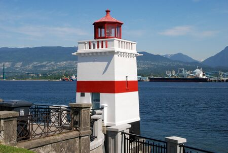 A white lighthouse with a red stripe at Brockton Point on the seawall in Vancouver, British Columbia.