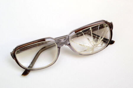opthalmology: old glasses with broken glass on a white background Stock Photo