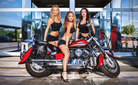 motorcycles: Three girls posing in a car wash, along with a custom bike. The first blonde, wavy hair. The second on the bike, brown. The third right, wavy hair brown.