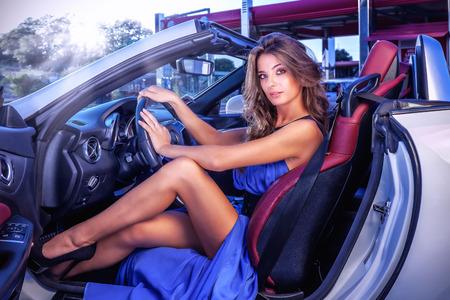 piernas: La muchacha atractiva se muestra con vestido azul largo que se sienta en el coche descapotable blanco. Foto de archivo