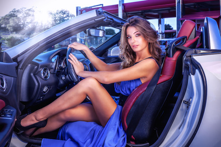 Sexy girl is shown with long blue dress sitting in white car cabriolet.