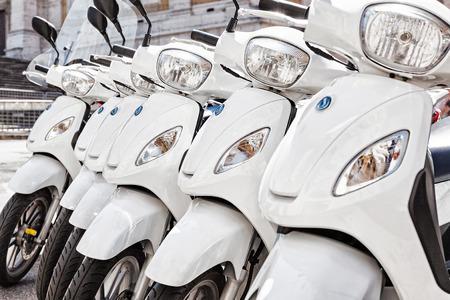 白いスクーターのシリーズは、都市内の行に駐車されています。