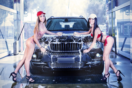 Girls in bathing suits, a car wash by hand with sponge and foam.