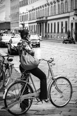 answer phone: Milan, Italy - August 26, 2013: Girl on a bicycle in the street stops to answer a phone call. We are in Via Alessandro Manzoni, the background some buildings and the tracks of the tram line.