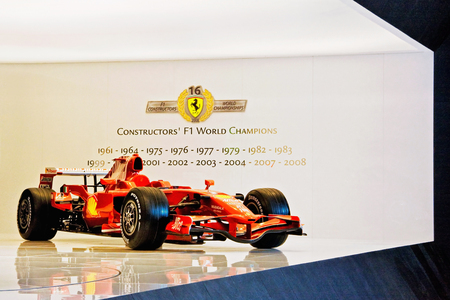 formula 1: Bologna, Italy - December 4, 2008: Car model from Ferrari Formula 1, exposed during the Motorshow. On the wall are written the years when he won the world title from 1961 to 2008.