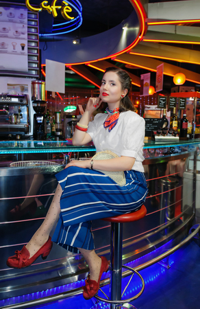 red shoes: Pin up girl style 60 years, he sits at the counter of a room waiting to get a drink. Brown hair, red lipstick, long skirt and red shoes.
