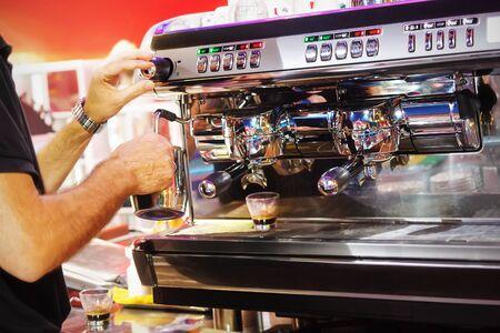 espreso: Barman prepares hot milk and espresso, for customers of the bar.