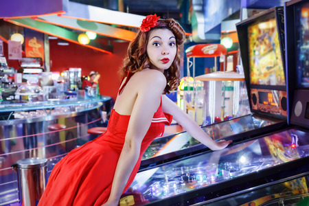 pinball: Style pinup girl in red dress, play pinball.