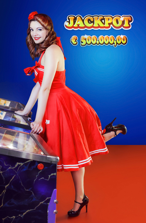 pinball: Girl in red dress pin up style, play pinball. Light blue background with Jackpot written five hundred thousand euro, and space for additional text. Stock Photo