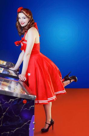 pinball: Girl in red dress pin up style, play pinball. Light blue background with space for additional text. Stock Photo