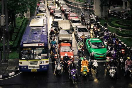 await: Bangkok, Thailand - August 16, 2012: Sukhumvit Road, at traffic lights, a line of cars, buses and motorbikes await the green to leave.