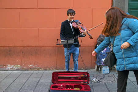 passerby: Naples, Italy - January 6, 2016: in a main street of the historic center of the city, a passerby from a dime to a street artist.