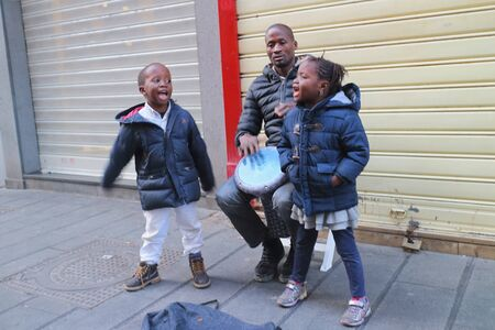 bongos: Naples, Italy - January 6, 2016 in a main street of the old town, an African man singing and playing the bongos, accompanied by his two children little ones.