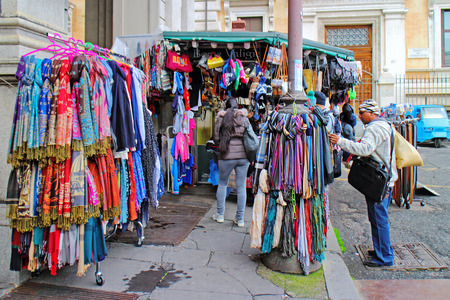 strangers: Rome, Italy - January 15, 2016: Some passersby stop in front of a kiosk for the sale of bags, accessories and scarves, in a corner of the station.