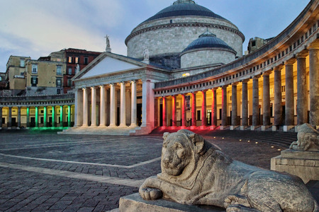 Piazza del Plebiscito in Naples, illuminated with the colors of the Italian flag. On the background of the colonnade surrounding the square in half, with the Royal Basilica of San Francesco di Paola.