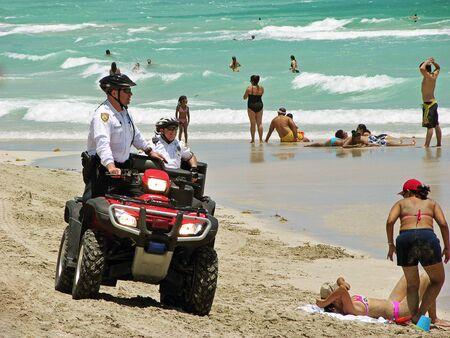ensuring: Miami, Florida, USA - May 28, 2007: Two policemen riding their quad-biking, patrolling the beach in Miami, ensuring the safety of persons. Editorial
