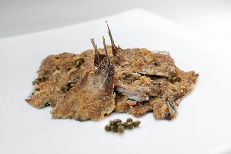 breadcrumbs: Anchovies baked with capers and breadcrumbs. Photographed in the studio, on the plate and a white background. Stock Photo