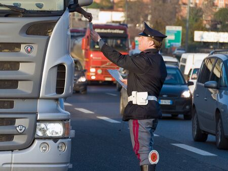 truck driver: Rome, Italy - January 18, 2008: Agent of the Italian traffic police receives documents from the driver of a truck during a routine check.