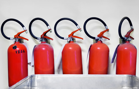 lined up: Set of five red fire extinguishers lined up, in the background a gray wall.