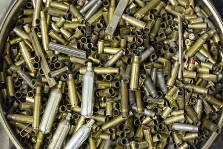 casings: Bucket full of shell casings of bullets used. Stock Photo