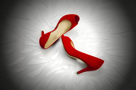 suffered: Two womens shoes red, rest on a plan full of broken glass fragments. The image symbolizes the continuing violence suffered by women who often end up victims of family killings. Stock Photo