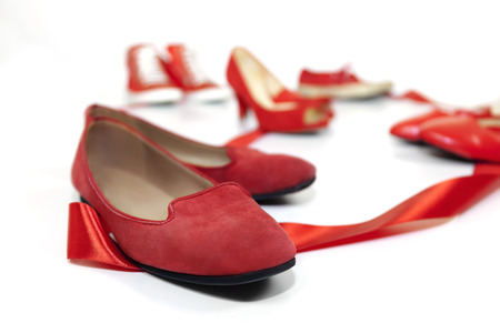 symbolized: Red shoes women of various models, are based on a white floor and are joined by a red ribbon, which is the common thread that unites them: violence against women, symbolized by red shoes. Stock Photo