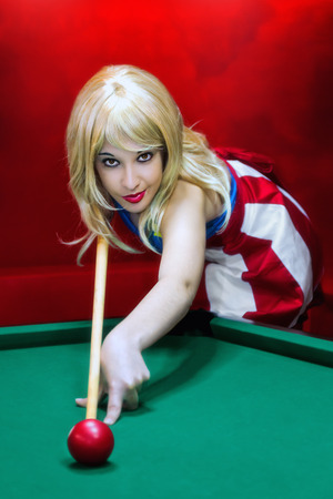 Blonde girl in pin-up style plays to the pool table Stock Photo