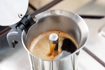 frothy: Espresso made at home, with steel mocha. coffee foam rises to the surface. Stock Photo