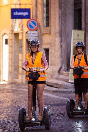 segway: Rome, Italy - August 3, 2016: Two girls pass through the narrow streets of the city center with the help of a modern segway. Editorial