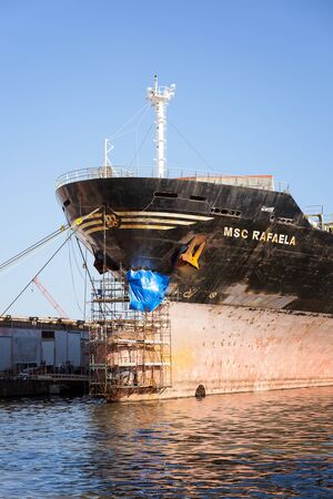 scaffolds: Naples, Italy - August 10, 2016: A ship docked in the port construction sites, is repaired by damage to the bow. Scaffolds were placed to allow workers to work on the hull. Editorial